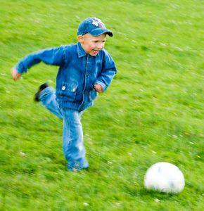 boy playing soccer in grass